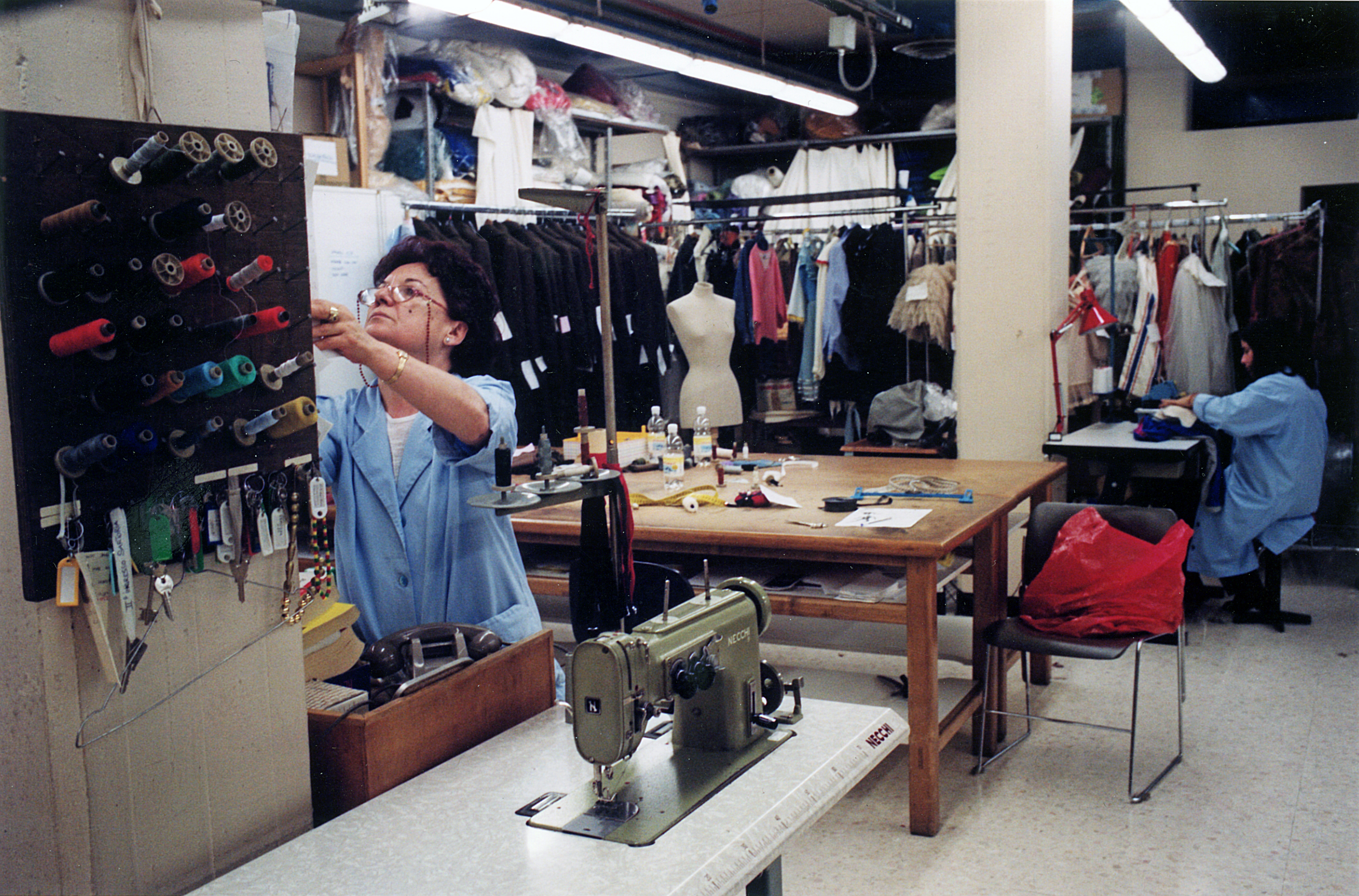 A view of the costume workshop in the midst of reels, sewing machines and clothes hangers